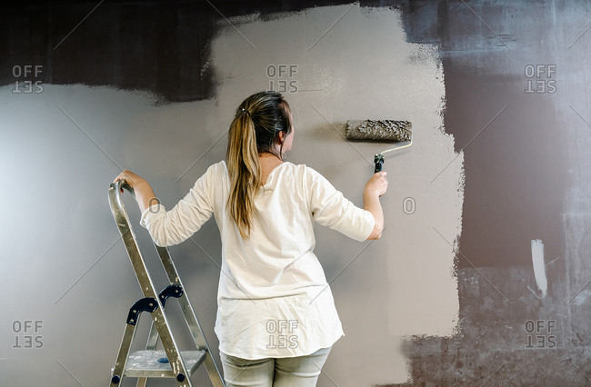 Woman on a ladder and using a roller to paint wall gray