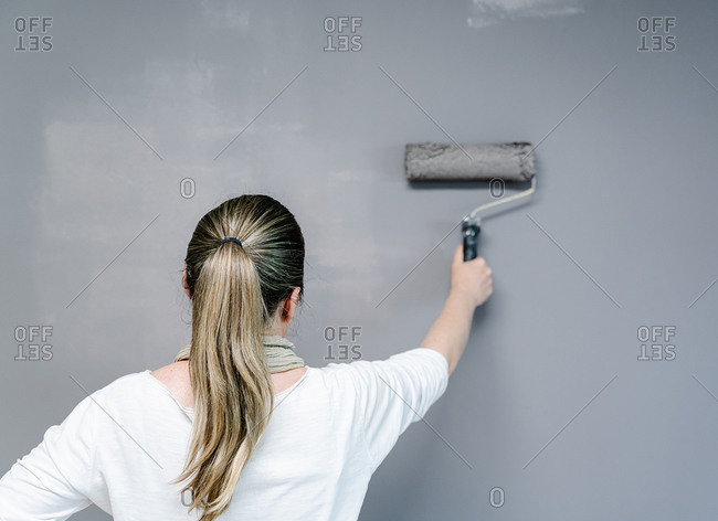 Back view of woman catching using a roller to paint a wall gray