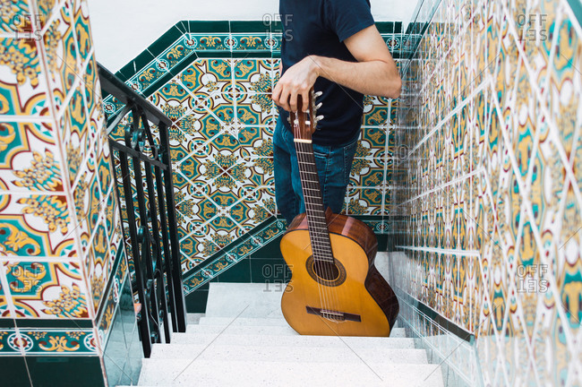 Crop man standing on a staircase with a Spanish guitar.