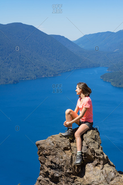 Hiker girl is on top of the mountain overlooking deep blue lake