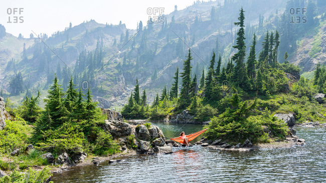 Woman is enjoying an afternoon in a hammock at the alpine lake
