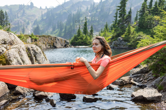 Woman is relaxing in a hammock at the alpine lake on local vacation