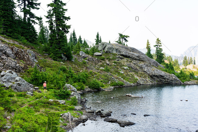 Bright hiker walking around the alpine lake on summer day in WA.