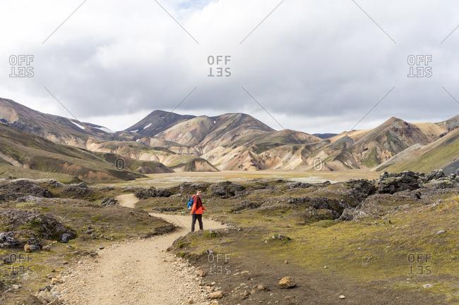 Male hiker walking down the empty rocky trail in Iceland