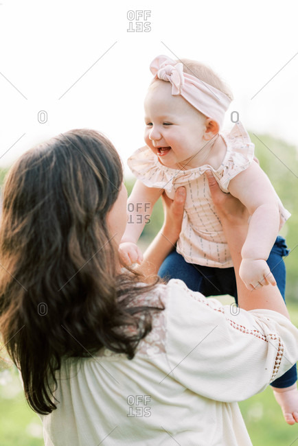 A cute one year old being held up by her mother.