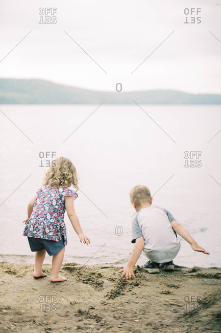Two children playing in the sand by the shore of a lake