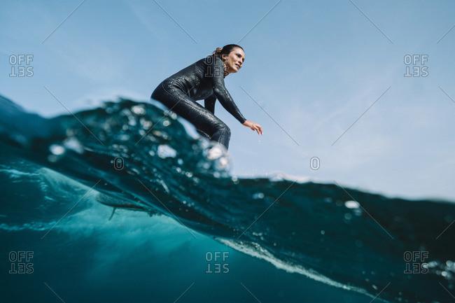 Close up split image of female surfer on a wave