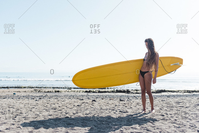 Portrait of a female surfer posing with longboard on the beach