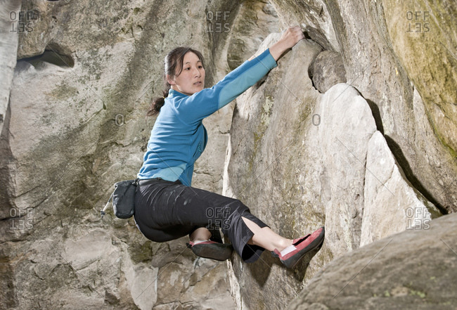 Mature woman bouldering in the forest of Fontainebleau close to Paris