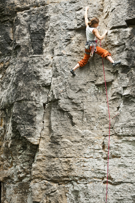 Young woman climbing rock face in France