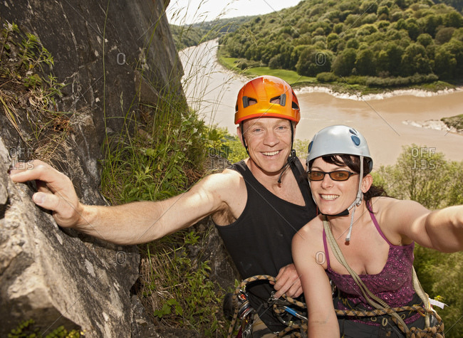 Couple climbing steep rock face in south Wales