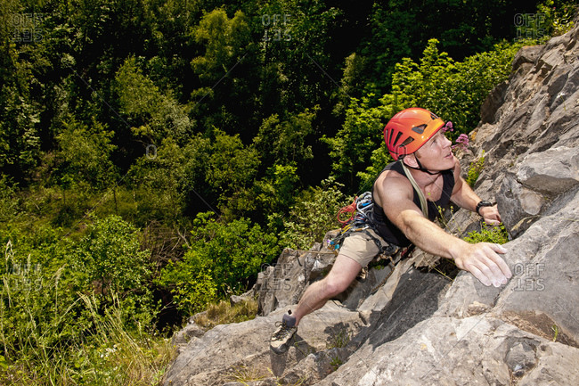 Man climbing limestone cliff in South Wales