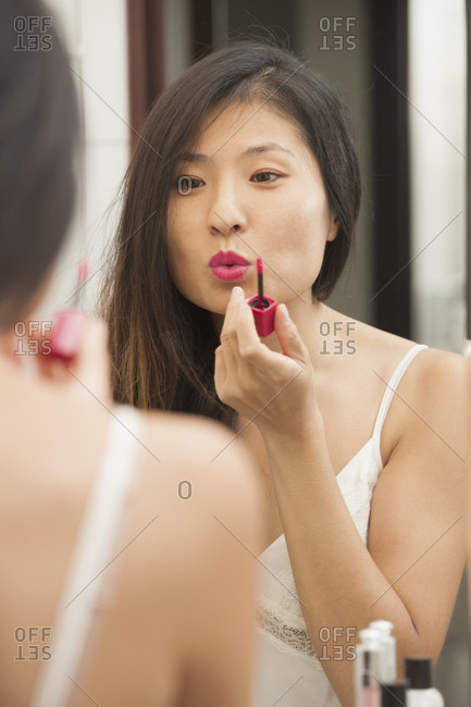 Beautiful woman applies lipstick while looking in the mirror