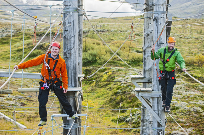 Two men balancing on high rope obstacle course in Iceland