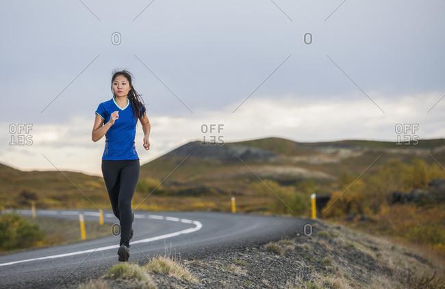 Beautiful woman jogging in rural area in Iceland