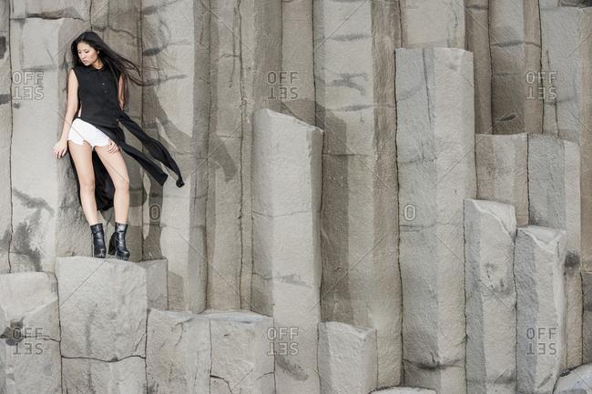 Beautiful woman posing on basalt rocks in Iceland