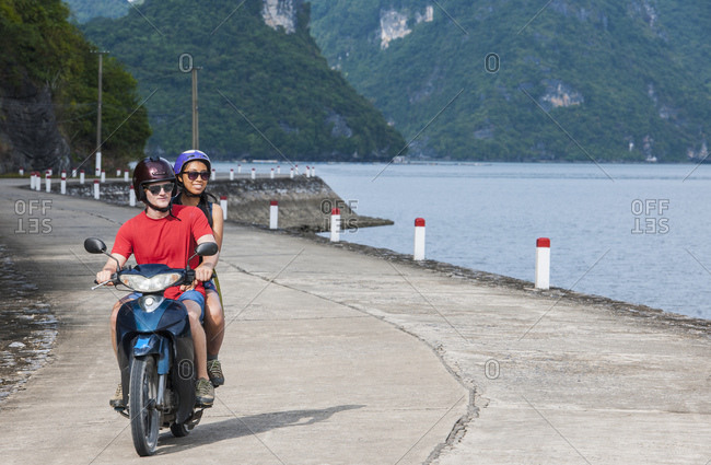 Young couple exploring Cat Ba Island on a motor scooter