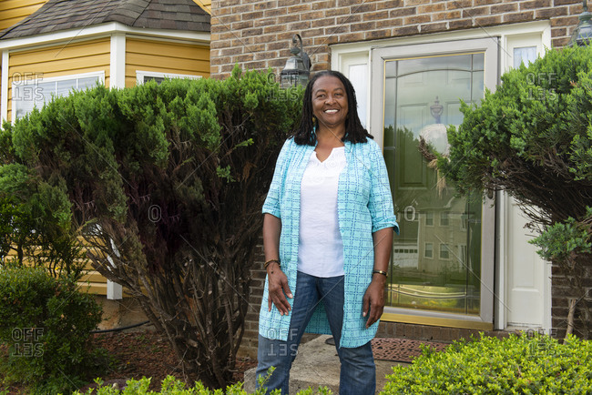 Smiling African-American woman standing in front of her house