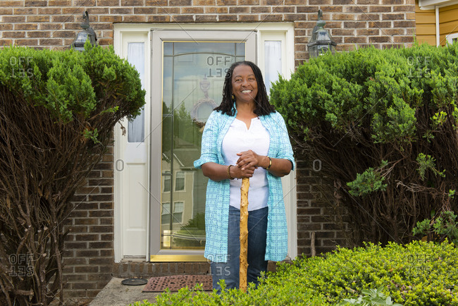 Portrait of an African-American woman standing in front of her house