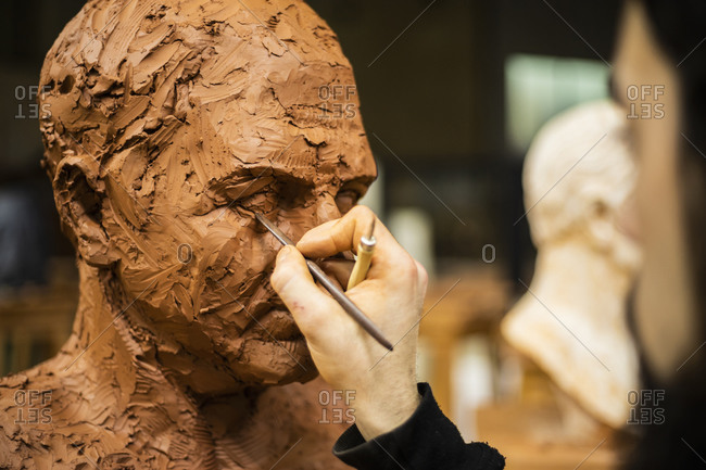 Hand of sculptor finishing a clay head eye