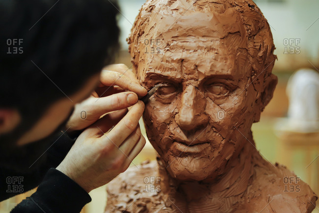 Close up of sculptor finishing a clay head eye in an art studio