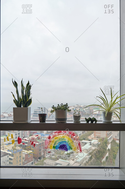 Potted Plants on a Window Sill in an Urban Apartment with a Child's Drawing Underneath