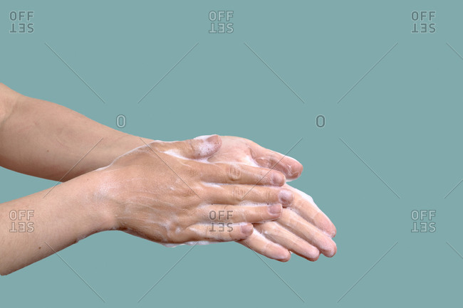 Woman wash hands on a blue background. Hygiene concept