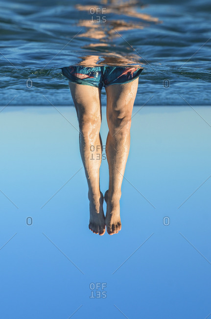 Young male legs coming out of the water. Surrealism