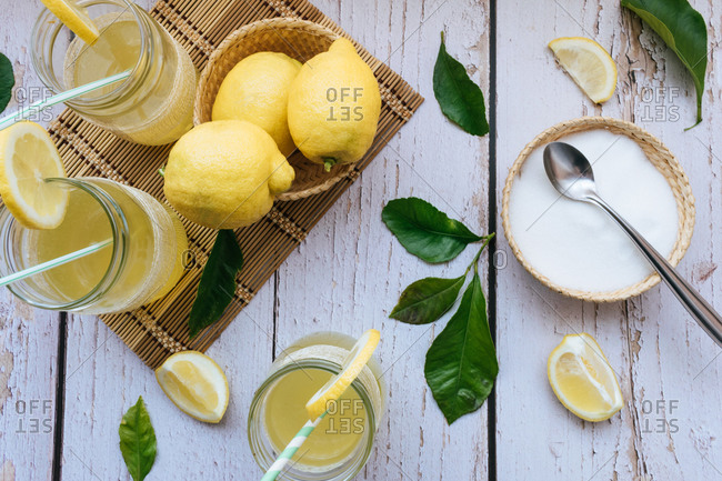 Top view of glasses of lemonade with lemons and sugar on a white table