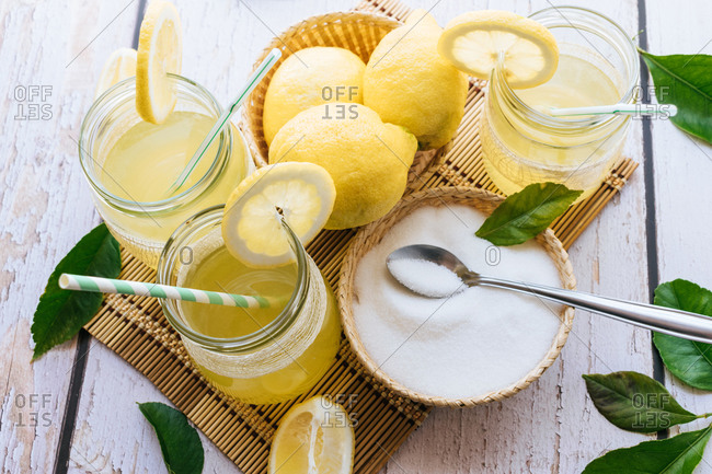 View of several glasses of fresh lemonade and lemons on a white table