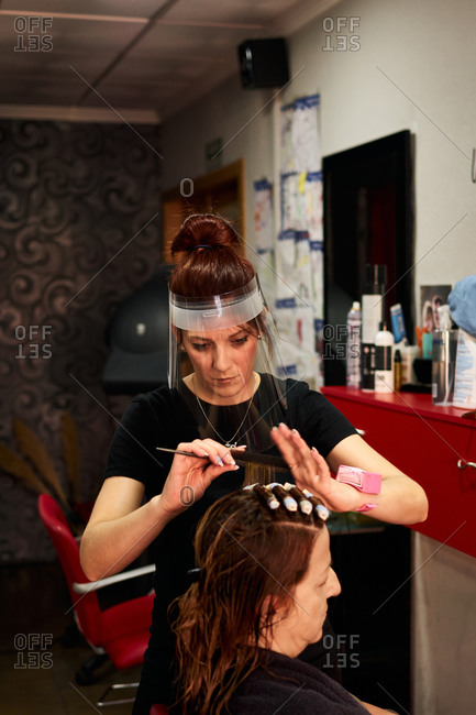 Hairdresser combs a client with a face shield in her salon