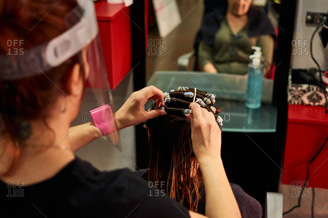 A close-up of a hairdresser combing a client with a face shield