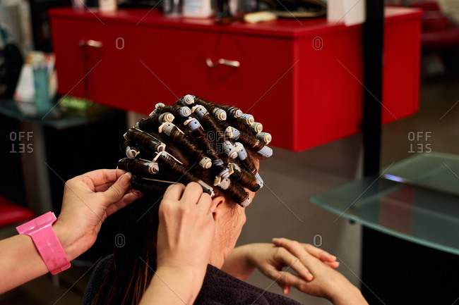 Close up shot of a hairdresser doing her client's curls