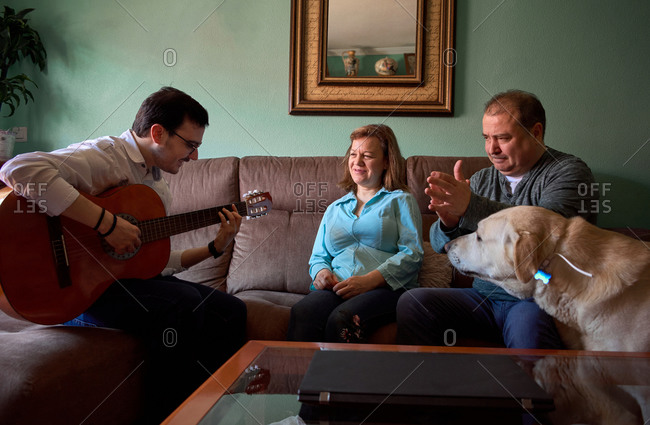 Family having fun while they're playing the guitar and singing at home