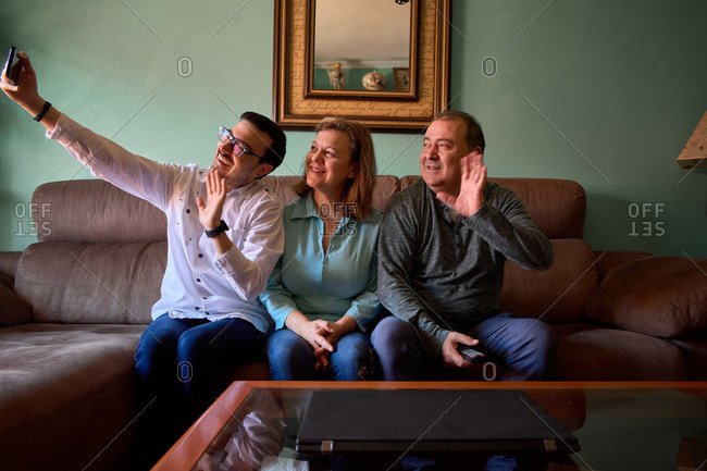 Family talks online with a smartphone in their living room