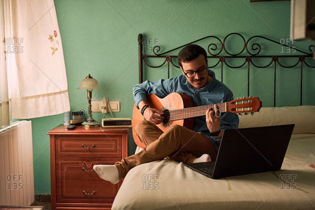 Young man practices with the guitar by looking at his laptop at home