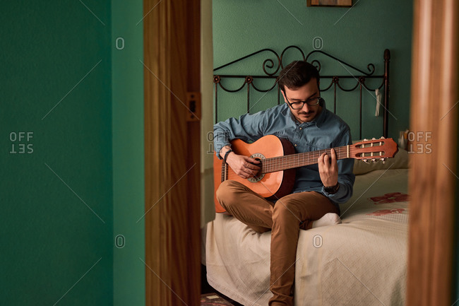 Young man plays guitar in a room in his house