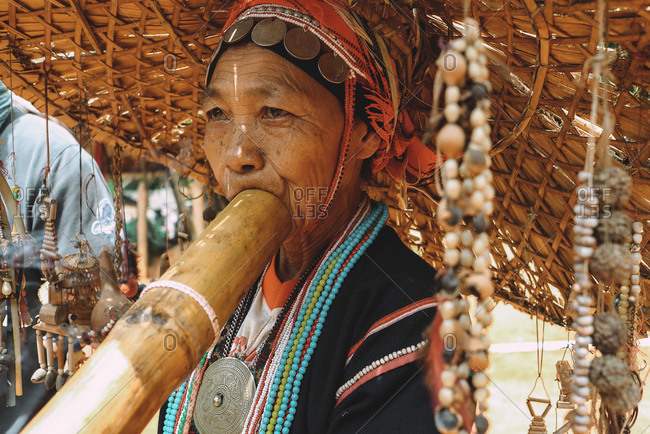 Chiang Mai, Thailand - July 3, 2020: Portrait of a woman from a Thai tribe playing a musical instrument.