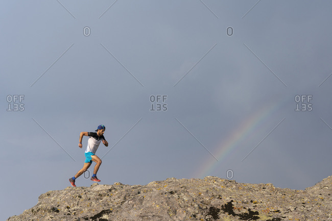 One man trail running on a rocky terrain with a rainbow
