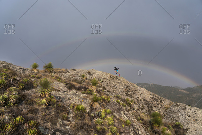 One man trail running up on a rock under a double rainbow