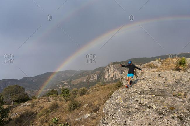 One man trail running on a rock under a rainbow