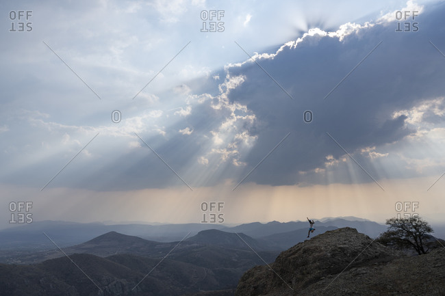 One man running downhill on a rock under a cloudy sky with sunrays