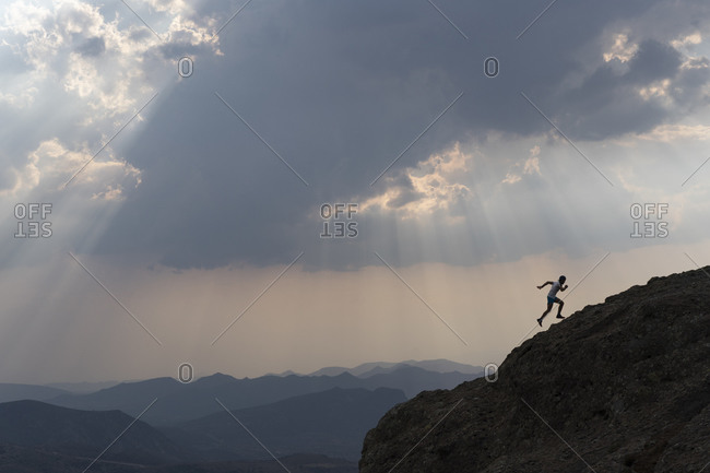 One man running up on a rock under a cloudy sky with sun rays
