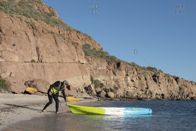 One woman getting ready to jump on a kayak at Carmen Island in Baja California.