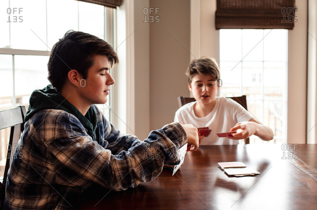 Two teenage boys playing cards at the kitchen table together.