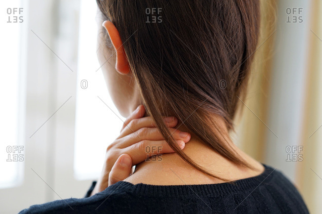 Woman with neck pain touching her neck. Neck pain concept.