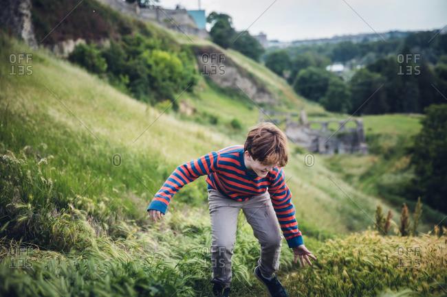 Boy Running Up A Grassy Hillside in Belgrade, Serbia