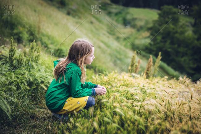 Child Looking Off Grassy Hillside in Belgrade, Serbia