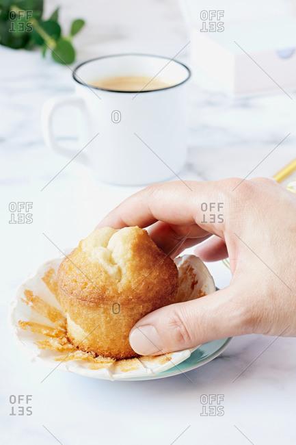 Woman's hand grabbing a homemade muffin.