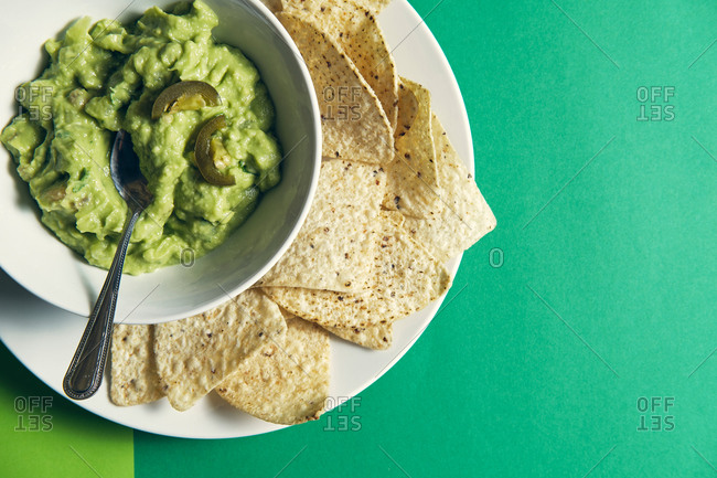guacamole sauce in a ceramic bowl on a green background